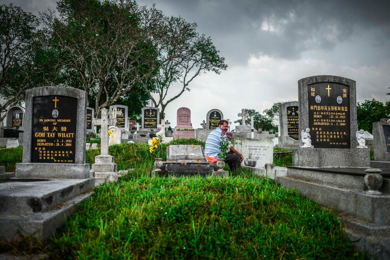"""Relative sits near the tomb stone of their departed love ones during All Souls Day festival at a cemetery outside Kuala Lumpur on November 2, 2015. All Souls Day is a day of prayer for the dead, particularly but not exclusively one's relatives which is observed on Nov 2 every year, also goes by its official name as """"The Commemoration of All the Faithful Departed"""". photo adib rawi yahya"""