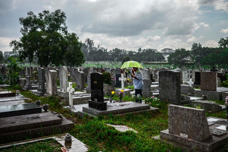 """A man offer prayers in rain at the tomb stone of their departed love ones during All Souls Day festival at a cemetery outside Kuala Lumpur on November 2, 2015. All Souls Day is a day of prayer for the dead, particularly but not exclusively one's relatives which is observed on Nov 2 every year, also goes by its official name as """"The Commemoration of All the Faithful Departed"""". photo adib rawi yahya"""
