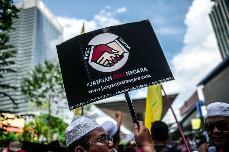 Malaysia's non-governmental organization (NGO) holds a placard in protest against the controversial Trans-Pacific Partnership Agreement (TPPA) as U.S. President Barack Obama attends the 27th Association of South-East Asian Nations (ASEAN) Summit in Kuala Lumpur on November 21, 2015. The U.S. President delivered Malaysia needs to decide whether it will join Trans-Pacific Partnership (TPP) by mid of January next year. photo Adib Rawi Yahya
