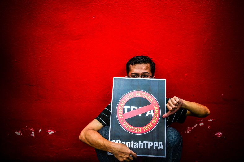 A man holds a placard in protest against the controversial Trans-Pacific Partnership Agreement (TPPA) as U.S. President Barack Obama attends the 27th Association of South-East Asian Nations (ASEAN) Summit in Kuala Lumpur on November 21, 2015. The U.S. President delivered Malaysia needs to decide whether it will join Trans-Pacific Partnership (TPP) by mid of January next year. photo Adib Rawi Yahya