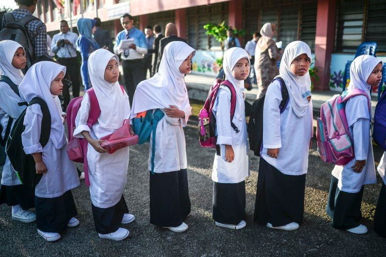 Year One pupils line up before enter their classroom for the first time during the first day school session outside Kuala Lumpur on January 4, 2016. photo Adib Rawi Yahya