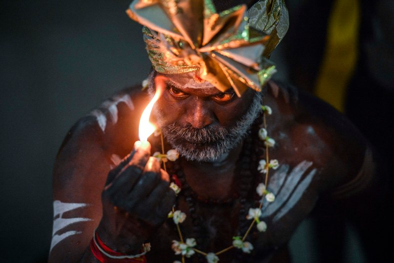 Malaysian Hindu devotees perform their religious rites before walking towards to the temple to make offerings during the Thaipusam Festival at Batu Caves outskirts of Kuala Lumpur on January 24, 2016. The Hindu festival of Thaipusam, which commemorates the day when Goddess Pavarthi gave her son Lord Muruga an invincible lance with which he destroyed evil demons, is celebrated by some two million ethnic Indians in Malaysia and Singapore. photo Adib Rawi Yahya