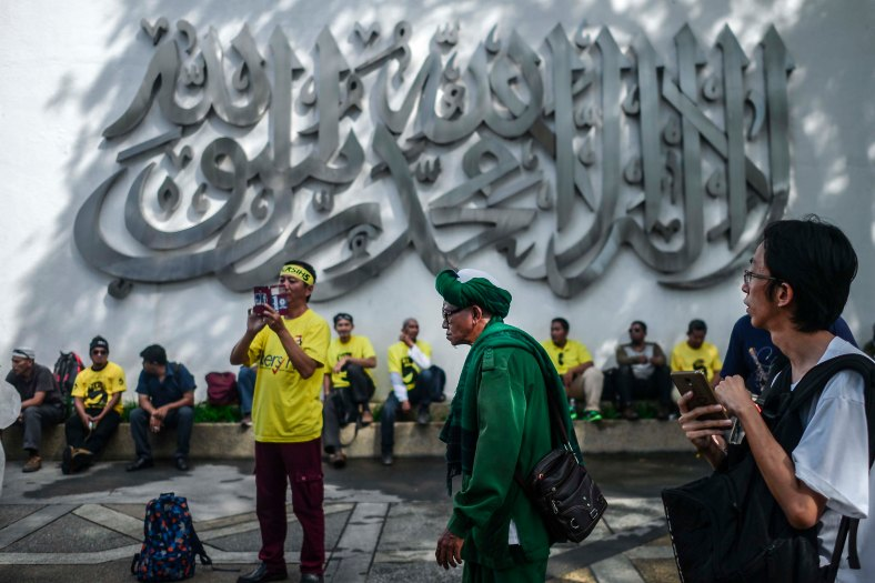 """Protesters sit near arabic word """"Lailahaillallah Muhammad Rasul Allah"""" means """"No God but Allah and Muhammad is the Messenger of God"""" as they gather at a street to step up pressure on Prime Minister Najib Razak to resign over alleged corruption during the Bersih 5.0 rally in Kuala Lumpur on November 19, 2016. Bersih 5.0 is the fifth such rally since 2007 where anti-government protesters demand clean elections, clean government, strengthened parliamentary democracy, the right to dissent and empowering the eastern state of Sabah and Sarawak. photo adib rawi yahya"""