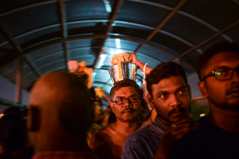 Malaysian Hindu devotees carry milk pots on their heads as perform their religious rites while walking towards to the temple to make offerings during the Thaipusam festival at Batu Caves outskirts of Kuala Lumpur on February 09, 2017. The Hindu festival of Thaipusam, which commemorates the day when Goddess Pavarthi gave her son Lord Muruga an invincible lance with which he destroyed evil demons, is celebrated by some two million ethnic Indians in Malaysia and Singapore. photo Adib Rawi Yahya